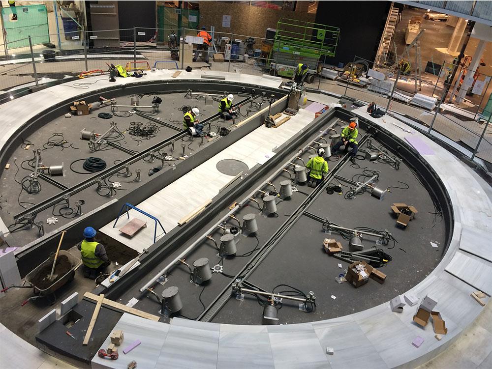 Blivande fontän, Mall of Scandinavia. Rund cirkel med gjutning av betong inuti. Flera arbetare som sitter ner och jobbar.